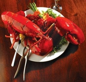Lobster on plate with lemon and asparagus on a table